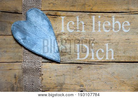 Burlap Ribbon And Heart On Wooden Table, German Text, Concept I Love You