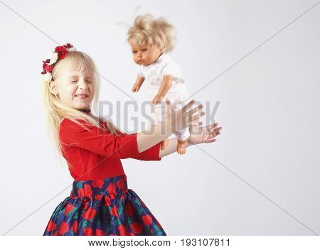 Little Happy Girl Playing A Doll, On A White