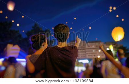 Teens in summer night with paper lantern
