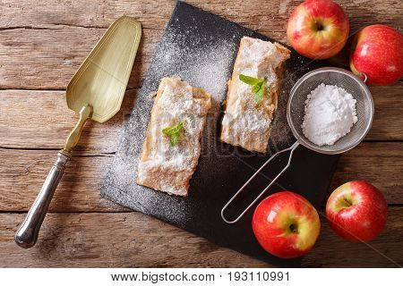 Apple Strudel Sprinkled With Sugar Powder Close-up On The Table. Horizontal Top View