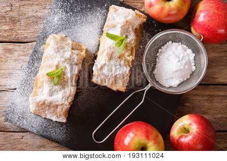 Austrian Food: Apple Strudel With Powdered Sugar And Mint Closeup On The Table. Horizontal Top View