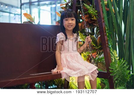 Asian Chinese Little Girl Sitting On A Swing