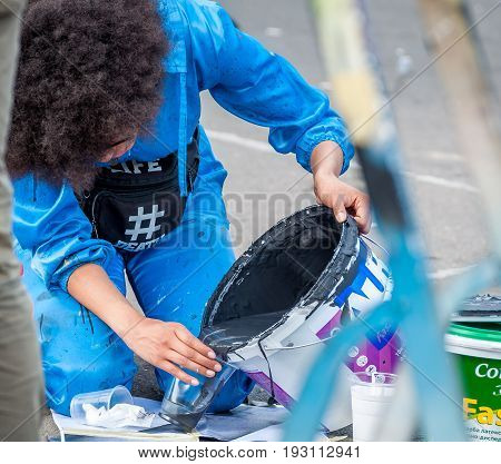 Ukraine Nikolaev 24.06.2017: Festival of graffiti dedicated to the Day of Youth. The central square of the city. Young beautiful African-American girl Sandra Sambo is preparing to draw graffiti.