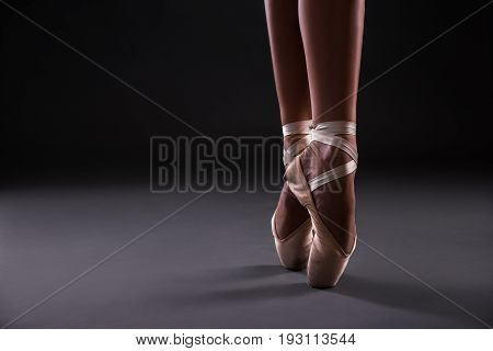Close Up Of Of Ballet Dancer's Feet Over Gray