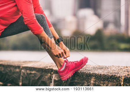 Running shoes tying laces runner healthy lifestyle woman getting ready to run. Healthy lifestyle jogging motivation closeup of feet or footwear.