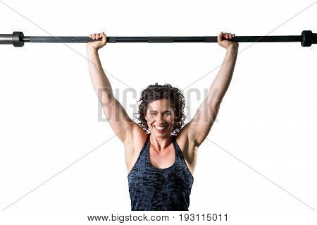 A happy and confident muscular female trainer easily holds an unloaded barbell over her head. There is a isolation path.