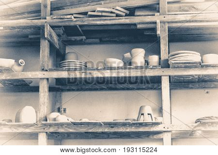 Bright pottery. Many white, not painted clay pottery standing on wooden shelves. Old vintage style.