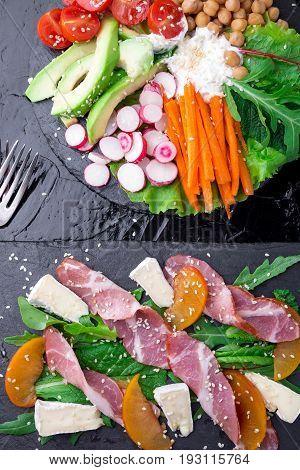 Two Different Salads Om Black Stone Slate. Vegan Salad. Meat Salad. Salad With Ham Jamon Serrano, Ca