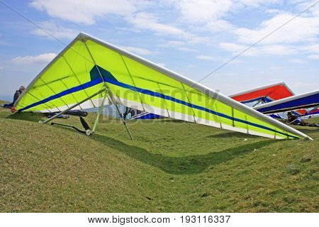 Hang gliders on a hill prepared to fly