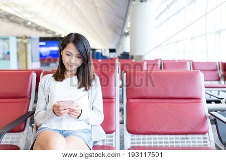 Young Woman use of cellphone in departure area of airport
