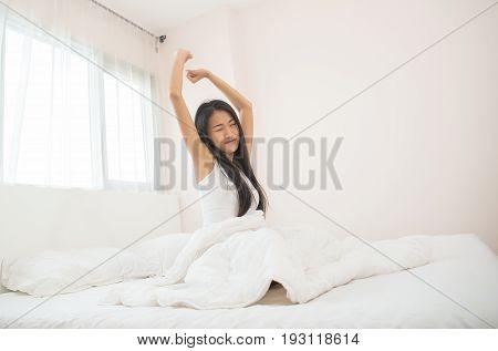Attractive asian woman awaking on the bed (sleep)