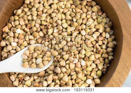 Whole grain buckwheat in wood bowl white spoon