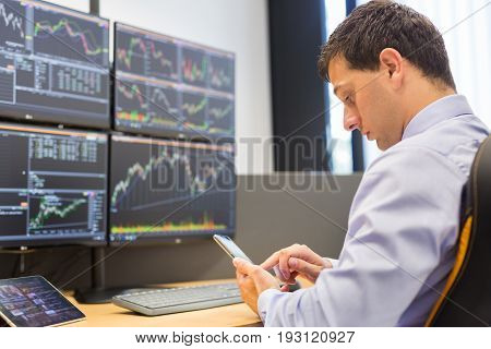 Stock broker trading online while accepting orders by phone. Trader's office with multiple computer screens full of index charts and data analyses.