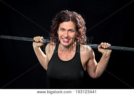A smiling weight trainer poses for the camera with a barbell on her back. She is on a black background and is cross lit.