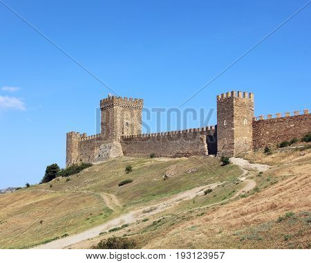 The medieval ruins of the Genoese fortress in Sudak in the Crimea on the mountain on the shore of the Black sea. Tower with battlements and a fortified wall built of stones.