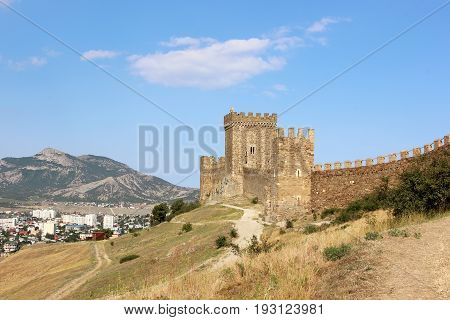 Medieval Tower in the Genoese fortress in Sudak on the background of the city and mountains. Crimea.