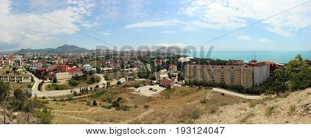 Panorama of Sudak the view of the city and the Black sea in a summer Sunny day. Crimea Russia.