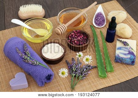 Medicinal herbs, flowers and ingredients for skincare with cleansing accessories on bamboo over oak background.