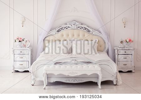 Luxury bedroom in light colors with golden furniture details. Big comfortable double royal bed in elegant classic interior.