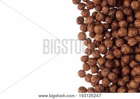 Chocolate balls corn flakes isolated with copy space background. Cereals texture.