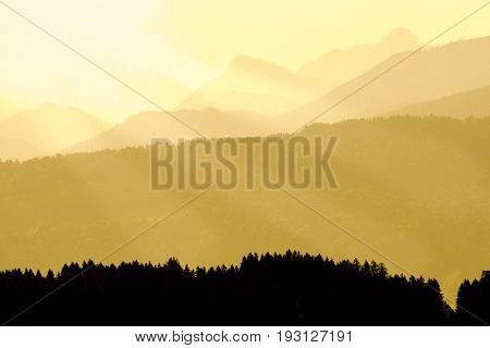 Beautiful view of mountain ranges silhouettes and valleys with bright orange back light and sunbeams. Allgau Alps.