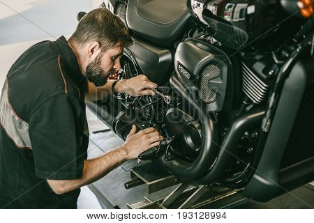 Serious young man repairing his motorcycle in bike repair shop. Mechanic fixing motocycle engine