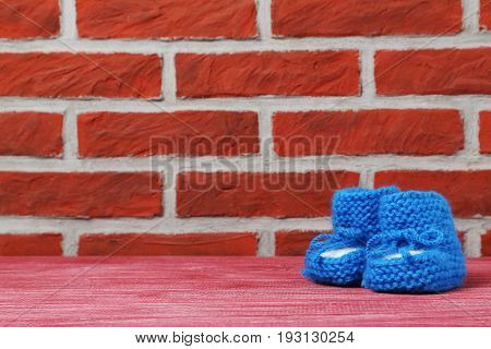 Baby's bootees on the brick wall background