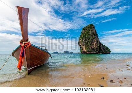 A Wooden Thai Boat With A Motor On The Background Of A High Cliff In The Andaman Sea