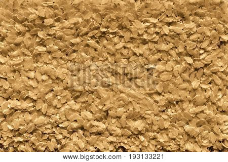 the textured background from granular flakes of an abstract form of brown color