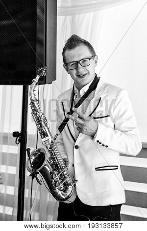 Saxophonist in white jacket playing the saxophone. Saxophonist jazz man with saxophone on wedding party