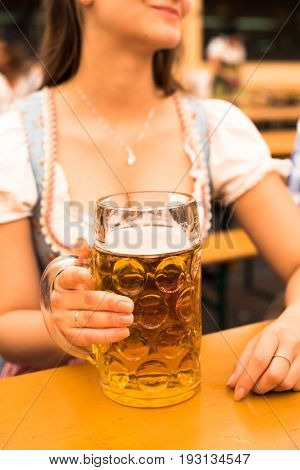Beautiful young woman in traditional Bavarian Dirndl with beer stein at Munich Oktoberfest
