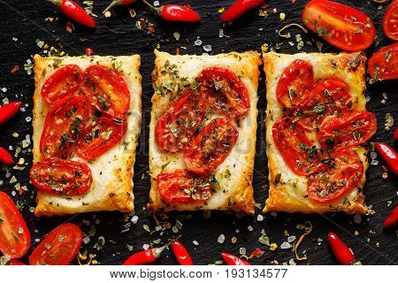 Puff pastry with tomatoes, chili peppers and herbs. Delicious vegetarian appetizers on black background