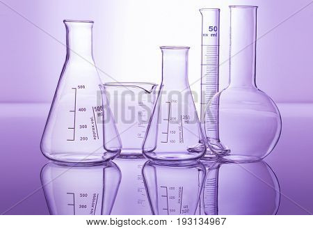 chemical glassware isolated on reflective surface in violet background