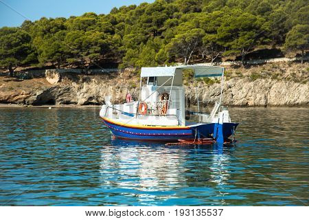 Boat in the bay in Assos village Kefalonia island Greece. Greek Islands cityscape.