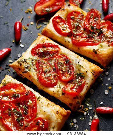 Puff pastry with tomatoes and herbs. Delicious vegetarian appetizer. Mini french pastry tart