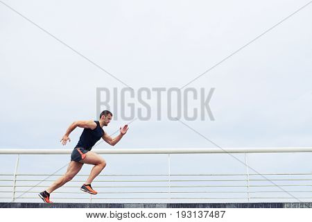 Young athlete running fast outdoors. Wearing sport cloth, doing wide step, demonstrating healthy way of life, wide shot