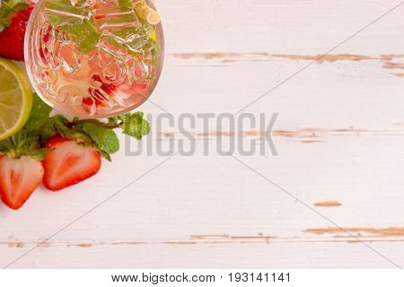 Top view strawberry lemon soda in glass on rustic wood table with blank space. Infused water ingredients with strawberry lemon or lime and water decorated with mint leaf ready to served. Homemade strawberry lemon soda on white plank.