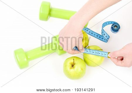 Hands Holding Cyan Flexible Ruler And Measuring Apple
