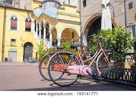 Ferrara, Italy -  - June, 8, 2017: bicycles stand on a parking in a center of Ferrara, Italy