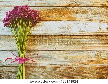 bouquet of beautiful purple allium flowers tied with a purple ribbon on wooden retro background with space for text. Flat lay top view