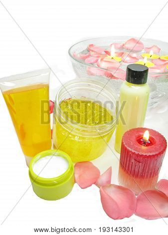 spa candles bowl with pink water with rose petals and cremes