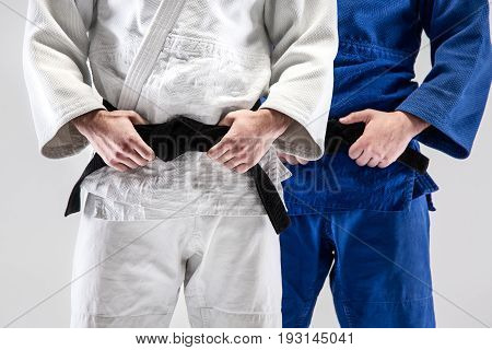 The two judokas fighters posing on gray studio background