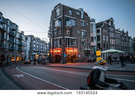 Amsterdam Netherlands - 25 April 2017: Adult rides a bicycle in historical part of Amsterdam with typical traditional houses against The Coffeeshop Reefer with legal soft drugs in evening.