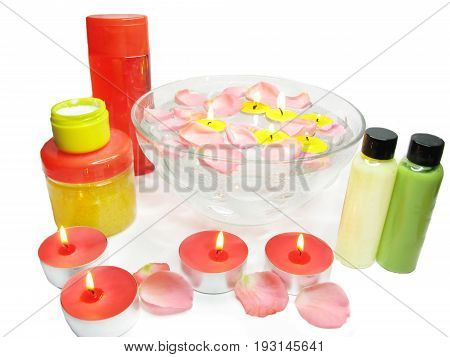 spa bowl with pink water with rose petals and shampoo cremes