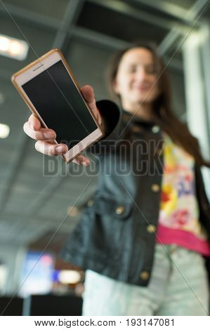 Smartphone mobile or cell phone modern device in hand of blurred girl or woman indoors on ceiling background. Technology 3G 4G. Communications and internet