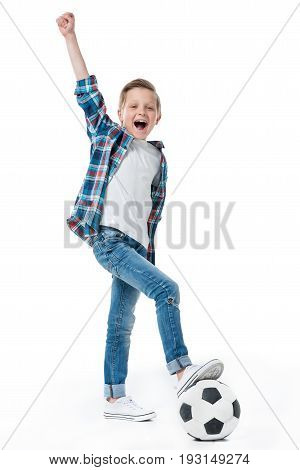 Cute Little Boy Standing With Soccer Ball And Celebrating Success With Fist Up