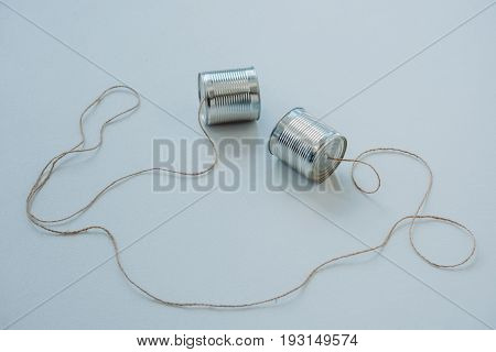 Close Up Of Aluminium Tin Cans Connected With Rope On Grey Surface, Tin Cans Telephone