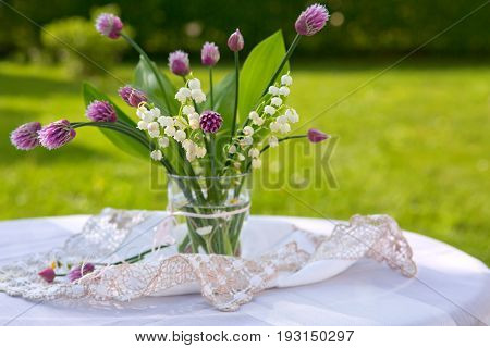 Lilly of the valley flowers in glas vase on the table with tablecloth.