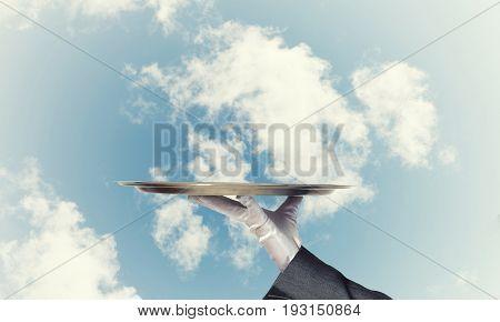 Butler hand in white glove presenting empty tray