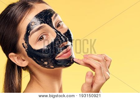 Woman on yellow background, black coal cosmetic face mask.